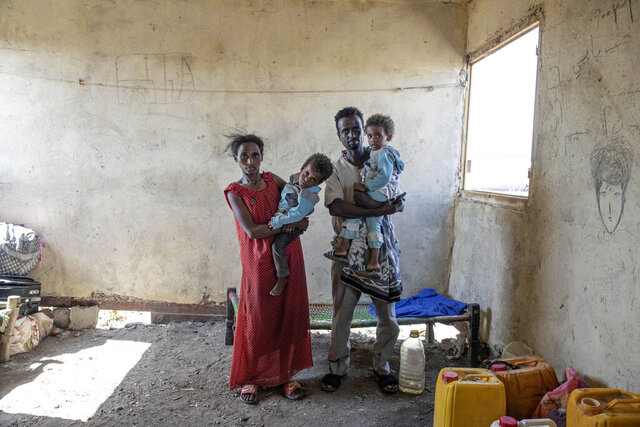 Tesfaalem Germay, 34, an ethnic Tigrayan survivor from Mai-Kadra, Ethiopia, poses for a photograph with his wife Bethlehem, 21, and their twin daughters inside a temporary shelter at Village 8, the transit center near the Lugdi border crossing, eastern Sudan, Nov. 22, 2020. Witnesses say hundreds of civilians were slaughtered in Mai-Kadra, but they disagree about who killed whom.