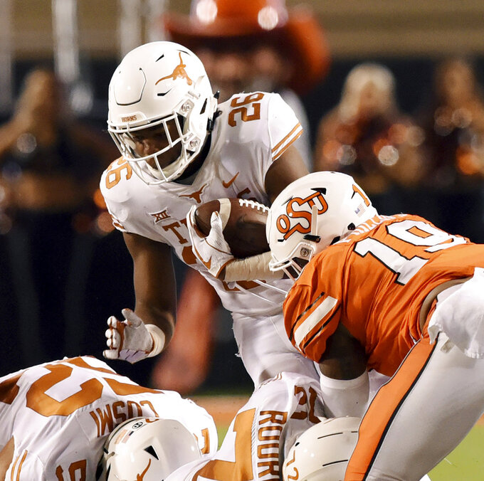 Texas running back Keaontay Ingram (26) struggles to get past Oklahoma State linebacker Justin Phillips (19) in the first half of an NCAA college football game in Stillwater, Okla., Saturday, Oct. 27, 2018. (AP Photo/Brody Schmidt)