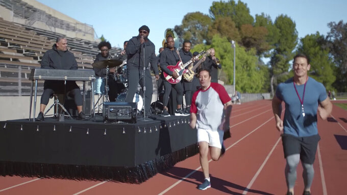 """This undated image provided by Michelob ULTRA shows John Cena, right, Jimmy Fallon, center, and the Roots in a scene from the company's 2020 Super Bowl NFL football spot. Wrestler-turned-actor John Cena tries to convince Tonight Show host Jimmy Fallon that there's a """"lighter side"""" to working out, with cameos by Tonight show band The Roots and runner Usain Bolt.  (Michelob ULTRA via AP)"""