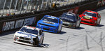 Sheet metal hangs from the car of Chase Briscoe after being involved in a crash during a NASCAR Xfinity Series auto race as Timmy Hill (66), Spencer Boyd (76) and Garrett Smithley (0) follow on Saturday, April 14, 2018 in Bristol, Tenn. (AP Photo/Wade Payne)