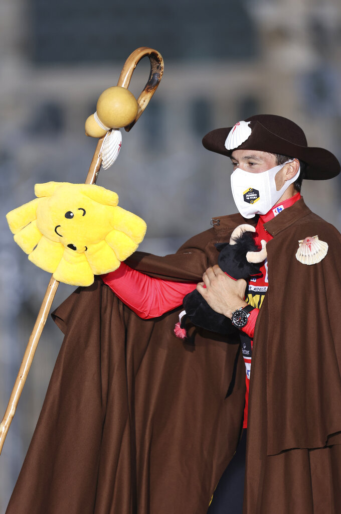 Primoz Roglic dressed as a traditional Pilgrim who walks the Way of St. James to Santiago, stands on the podium after winning the Vuelta Cycling race in Santiago, Spain, Sunday, Sept. 5, 2021. (AP Photo/Luis Vieira)