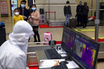 Passengers wearing face masks to protect against the spread of new coronavirus watch as a worker in a protective suit monitors a temperature scanner at Hankou train station after of the resumption of train services in Wuhan in central China's Hubei Province, Wednesday, April 8, 2020. After 11 weeks of lockdown, the first train departed Wednesday morning from a re-opened Wuhan, the origin point for the coronavirus pandemic, as residents once again were allowed to travel in and out of the sprawling central Chinese city. (AP Photo/Ng Han Guan)