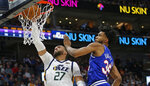 Utah Jazz center Rudy Gobert (27) dunks next to Sacramento Kings forward Marvin Bagley III (35) during the second half of an NBA basketball game Saturday, Jan. 18, 2020, in Salt Lake City. (AP Photo/Rick Bowmer)