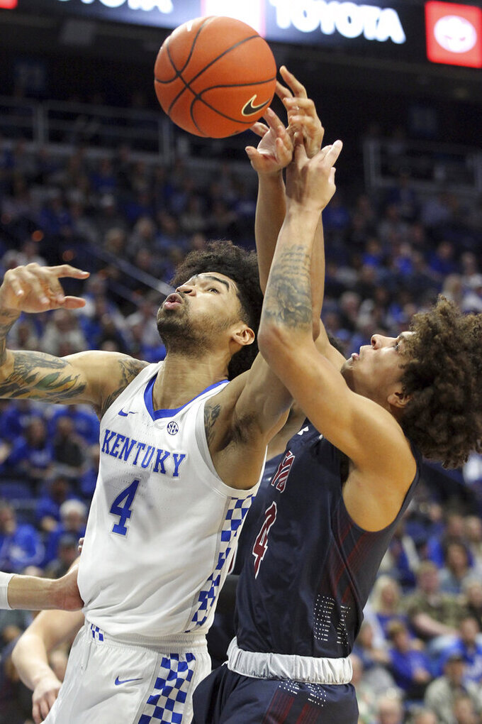 Kentucky's Nick Richards, left, and Fairleigh Dickinson's Brandon Powell, right, battle for a rebound during the first half of an NCAA college basketball game in Lexington, Ky., Saturday, Dec. 7, 2019. (AP Photo/James Crisp)