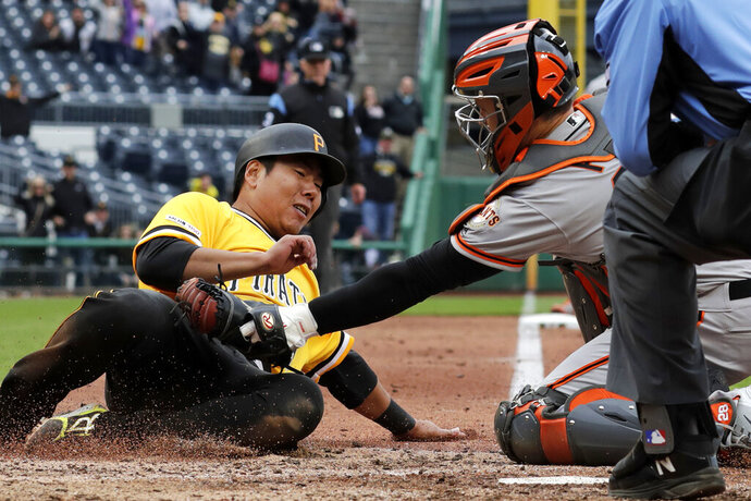 San Francisco Giants catcher Buster Posey tags out Pittsburgh Pirates' Jung Ho Kang, left, attempting to score the tying run on a double to right field by Bryan Reynolds during the ninth inning of a baseball game in Pittsburgh, Sunday, April 21, 2019. The Giants won 3-2.(AP Photo/Gene J. Puskar)