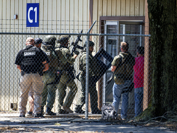 Law enforcement enter the C1 building to the west of the Bunn-O-Matic warehouse during an active shooter situation, Friday, June 26, 2020, in Springfield, Ill. Police say officers are searching for a gunman at a warehouse in the Illinois state capital after at least one person was shot and wounded. (Justin L. Fowler/The State Journal-Register via AP)