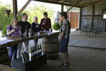 In this Wednesday, Nov. 6, 2019 photo, Mark Dankowski, right, leads a tasting for a group of people visiting the Soda Rock Winery in Healdsburg, Calif. The winery's main building was incinerated in the recent wildfires, but visits and tastings continue at a barn on the winery property. Despite a late October blaze that raged through one of the world's best-known wine-growing regions. forcing evacuations in two mid-sized towns, wine production in Sonoma County escaped largely unscathed. (AP Photo/Eric Risberg)