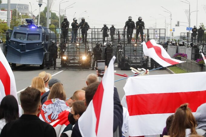 FILE - In this Aug. 23, 2020, file photo, demonstrators face a roadblock manned by riot police during a protest in Minsk, Belarus. With  protests in Belarus now in their third week — including rallies that brought out an estimated 200,000 people in Minsk for the last two Sundays — President Alexander Lukashenko is moving to squelch the demonstrations gradually with vague promises of reforms mixed with threats, court summonses and the selective jailing of leading activists. (AP Photo/Dmitri Lovetsky, File)