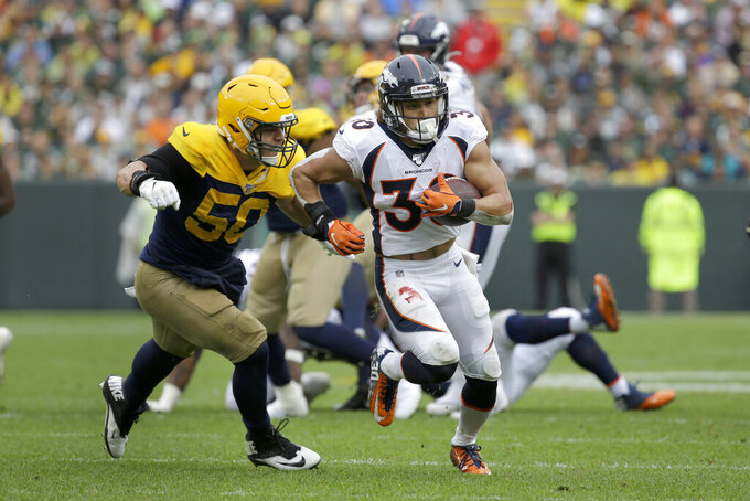 Denver Broncos running back Phillip Lindsay, right, runs with the ball as Green Bay Packers inside linebacker Blake Martinez (50) defends during the first half of an NFL football game Sunday, Sept. 22, 2019, in Green Bay, Wis. (AP Photo/Mike Roemer)