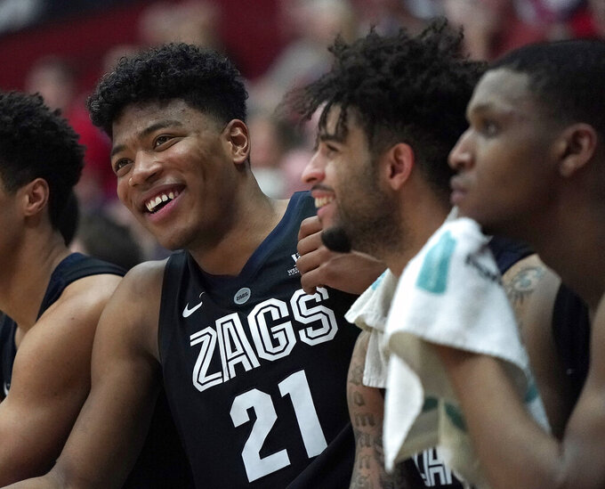 Gonzaga forward Rui Hachimura (21) and teammate Josh Perkins smile as they sit on the bench at the end of the team's NCAA college basketball game against Santa Clara on Thursday, Jan. 24, 2019, in Santa Clara, Calif. Gonzaga won 98-39. (AP Photo/Tony Avelar)