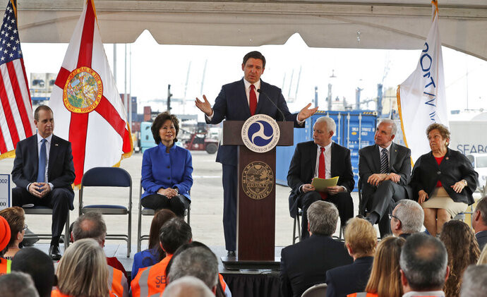 Florida Governor Ron DeSantis, center, gestures as he speaks during a news conference with U.S. Secretary of Transportation Elaine L. Chao, second from left, Rep. Mario Diaz-Balart, R-Fla., left, PortMiami Director Juan Kuryla, third from right, Miami-Dade County Mayor Carlos A. Gimenez, second from right, and Rep. Donna Shalala, D-Fla., right, at a news conference, Friday, Feb. 14, 2020, at PortMiami in Miami. Chao announced that the department has awarded more than $280 million in a new Port Infrastructure Development Program at 15 locations to improve facility and freight infrastructure. (AP Photo/Wilfredo Lee)