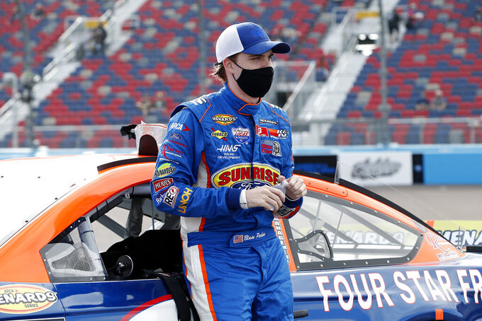 Blaine Perkins stands next to his race car on pit road prior to the ARCA Series auto race at Phoenix Raceway, Saturday, Nov. 7, 2020, in Avondale, Ariz. (AP Photo/Ralph Freso)