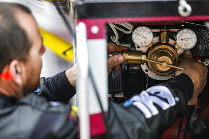 A member of Kyle Busch's pit crew adjusts the compressed air supply before a NASCAR auto race at Texas Motor Speedway, Saturday, March 30, 2019, in Fort Worth, Texas. (AP Photo/Brandon Wade)