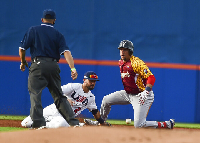 FILE - Venezuela's Hernan Perez, right, is safe at first base as United States' Eddy Alvarez (2) misses the catch in the first inning during an Americas qualifying tournament baseball game in Port St. Lucie, Fla., in this Saturday, June 5, 2021, file photo. Alvarez, having won a silver in speed skating at Sochi in 2014, helped the U.S. reach the Olympic baseball tournament and could become only the third American to win medals at the summer and winter Games.(Crystal Vander Weit/TCPalm.com via AP, File)