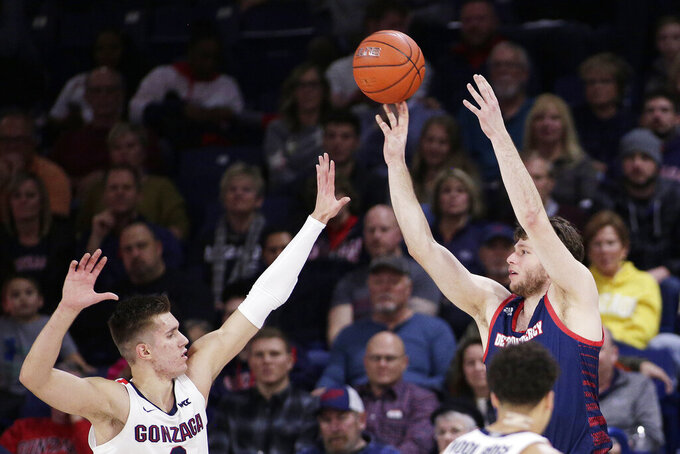 Detroit Mercy forward Willy Isiani, right, shoots over Gonzaga forward Filip Petrusev during the first half of an NCAA college basketball game in Spokane, Wash., Monday, Dec. 30, 2019. (AP Photo/Young Kwak)