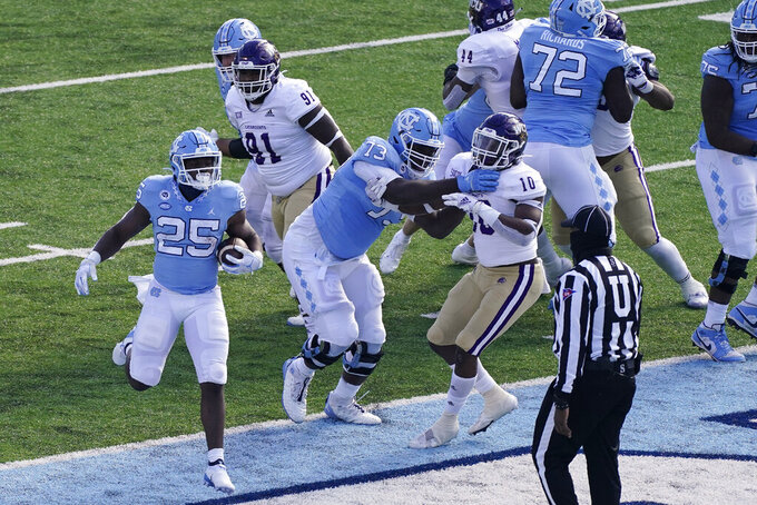 North Carolina running back Javonte Williams (25) scores a touchdown against Western Carolina during the first half of an NCAA college football game in Chapel Hill, N.C., Saturday, Dec. 5, 2020. (AP Photo/Gerry Broome)