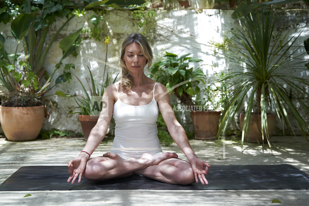 Mature woman meditating in lotus positing on exercise mat