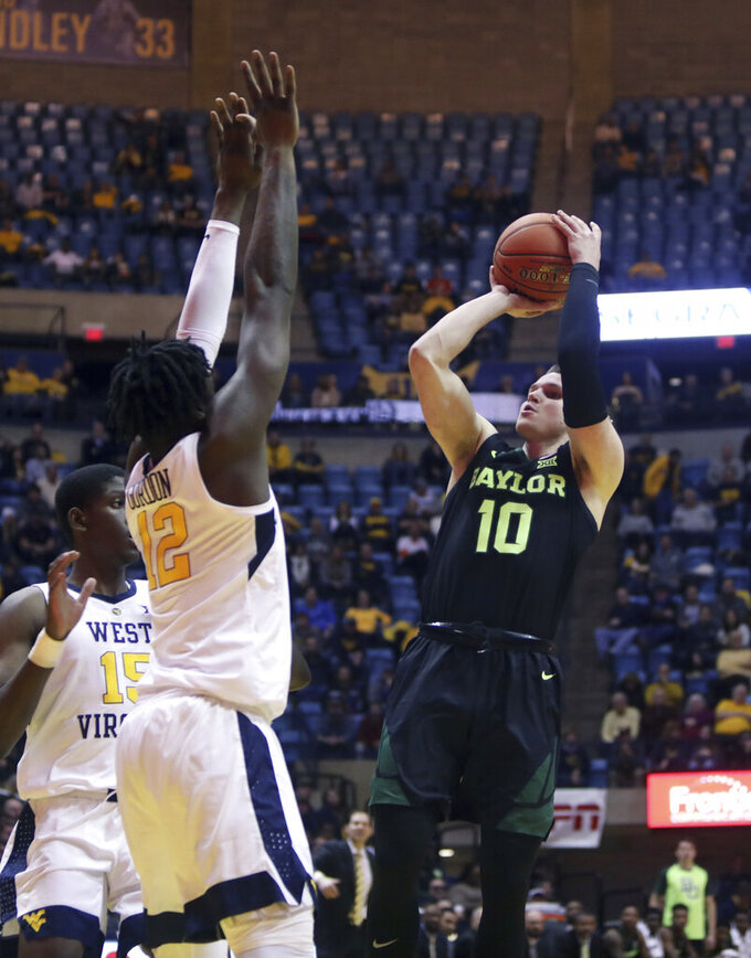 Baylor guard Makai Mason (10) shoots while defended by West Virginia forward Andrew Gordon (12) during the first half of an NCAA college basketball game Monday, Jan. 21, 2019, in Morgantown, W.Va. (AP Photo/Raymond Thompson)