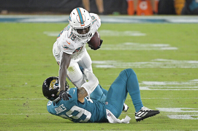Jacksonville Jaguars strong safety Josh Jones, left, brings down Miami Dolphins wide receiver Preston Williams (18) after a reception during the second half of an NFL football game, Thursday, Sept. 24, 2020, in Jacksonville, Fla. (AP Photo/Phelan M. Ebenhack)