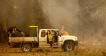 Jamie Fato prepares to stop an out of control fire entering Owen Whalan's property at Koorainghat, near Taree, New South Wales state, Tuesday, Nov. 12, 2019. Hundreds of schools remained closed across Australia's most populous state on Tuesday, Nov. 12, and residents were urged to evacuate woodlands for the relative safety of city centers as authorities braced for extreme fire danger. (Darren Pateman/AAP Images via AP)