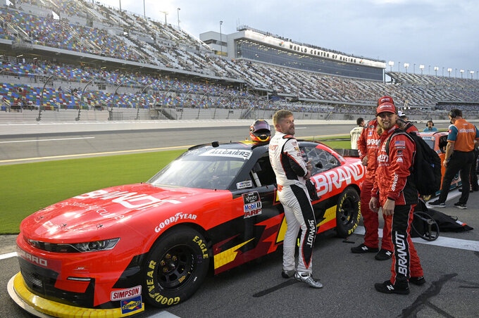 Justin Allgaier (7), left, stands next to his car on pit road before the start of a NASCAR Xfinity Series auto race at Daytona International Speedway, Friday, Aug. 27, 2021, in Daytona Beach, Fla. (AP Photo/Phelan M. Ebenhack)
