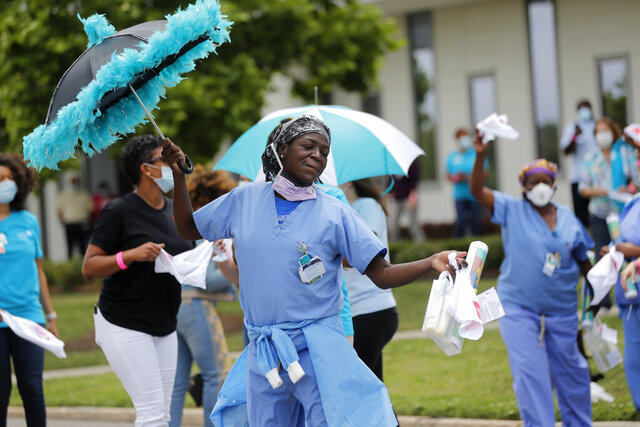 Healthcare workers at New Orleans East Hospital wave handkerchiefs and dance to a jazz serenade, as a tribute for their care for COVID-19 patients, by the New Orleans Jazz Orchestra, outside the hospital in New Orleans, Friday, May 15, 2020. A New York woman collaborated with the New Orleans Jazz Orchestra to put on what she calls a stimulus serenade to give moral support to front-line hospital workers and COVID-19 patients in New Orleans  (AP Photo/Gerald Herbert)