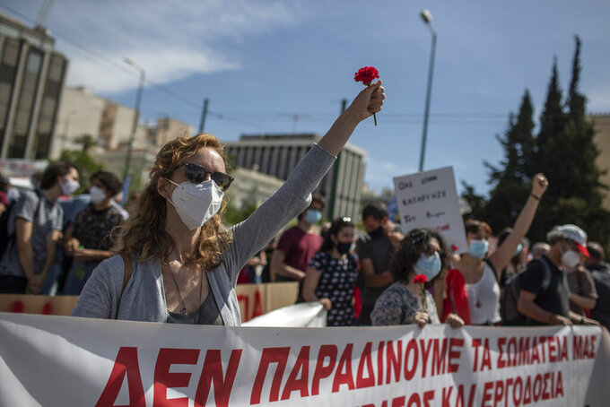 Members of the communist party-affiliated PAME wearing protective face masks hold red carnations, as they protest during a rally commemorating May Day, in Athens, Greece, Thursday, May 6, 2021. Demonstrators took part on a 24-hour strike against a new labour bill presented by the government protests. (AP Photo/Petros Giannakouris)