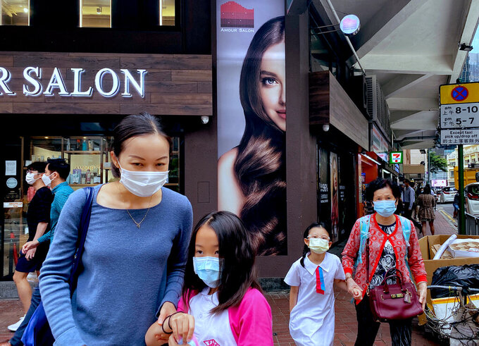 People wearing face masks to help protect against the spread of the coronavirus walk at a street in Hong Kong, Monday, April 26, 2021. Hong Kong and Singapore said Monday they would launch an air travel bubble in May, months after an initial arrangement that would allow tourists to fly between both cities without having to serve quarantine was postponed. Flights will begin from May 26.  (AP Photo/Vincent Yu)