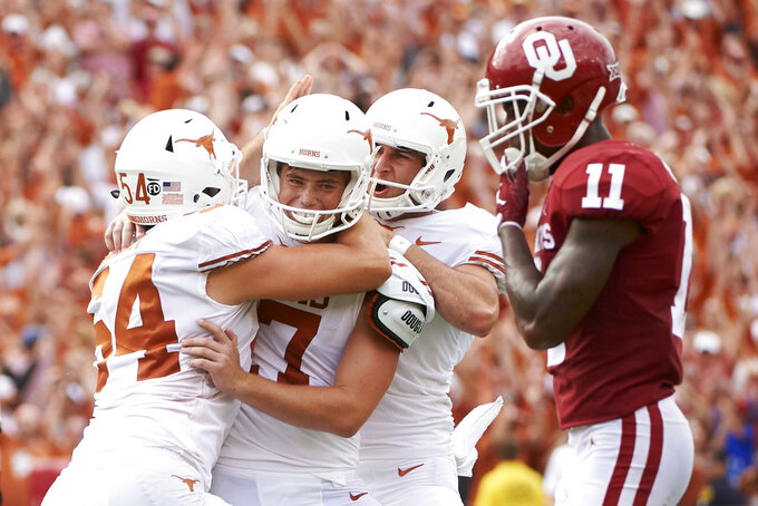 FILE - In this Oct. 6, 2018, file photo, Texas kicker Cameron Dicker (17) celebrates with teammates after kicking the game-winning field goal in the closing seconds of the second half of an NCAA college football game against Oklahoma at the Cotton Bowl in Dallas. The Texas-Oklahoma rivalry is never short on bad blood between the Big 12 border states (AP Photo/Cooper Neill, File