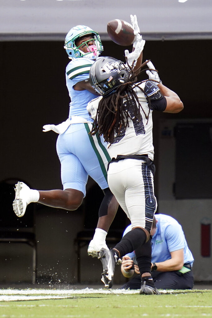 Tulane wide receiver Jha'Quan Jackson, left, makes a reception and runs 20-yards for a touchdown in front of Central Florida defensive back Aaron Robinson during the first half of an NCAA college football game, Saturday, Oct. 24, 2020, in Orlando, Fla. (AP Photo/John Raoux)