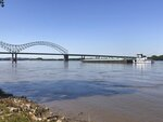 A boat hauling barges down the Mississippi River moves toward the Interstate 40 bridge linking Tennessee and Arkansas on Friday, May 14, 2021, in Memphis, Tenn. The U.S. Coast Guard reopened a section of the river near Memphis on Friday, three days after river traffic was shut down when a crack was found in the bridge. (AP Photo/ Adrian Sainz)