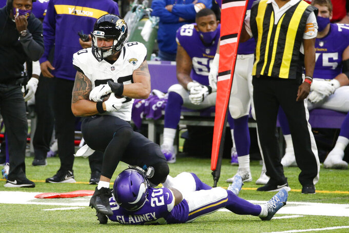 Jacksonville Jaguars tight end James O'Shaughnessy (80) tries to break a tackle by Minnesota Vikings cornerback Jeff Gladney (20) after catching a pass during the first half of an NFL football game, Sunday, Dec. 6, 2020, in Minneapolis. (AP Photo/Bruce Kluckhohn)