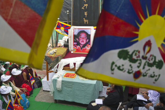 FILE - In this April 25, 2019, file photo, a portrait of the 11th Panchen Lama, Gendhun Choekyi Nyima, an important religious leader second only to the Dalai Lama in the Tibetan Buddhist hierarchy, is seen as exile Tibetans mark his birthday in Dharmsala, India. Tibet's self-declared government-in-exile marked the 25th anniversary of the disappearance of the boy named as Tibetan Buddhism's second highest figure by calling on China on Sunday, May 17, 2020 to account for his whereabouts. (AP Photo/Ashwini Bhatia, File)