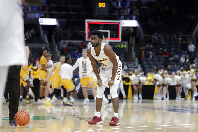 Loyola of Chicago's Keith Clemons reacts as members of Valparaiso celebrate in the background following an NCAA college basketball game in the quarterfinal round of the Missouri Valley Conference men's tournament Friday, March 6, 2020, in St. Louis. Valparaiso won 74-73 in overtime. (AP Photo/Jeff Roberson)