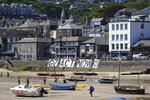 A giant banner from Extinction Rebellion is placed on a seawall outside the G7 meeting in St. Ives, Cornwall, England, Sunday, June 13, 2021. Leaders of the G7 wrap up three days of meetings in Carbis Bay Sunday, in which they discussed such topics as COVID-19, climate, foreign policy and the economy. (AP Photo/Jon Super)