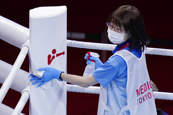 FILE - In this July 30, 2021, file photo, cleaning crew worker wipes down the ring before the men's heavyweight 91-kg boxing match at the 2020 Summer Olympics, in Tokyo, Japan. Tokyo Olympians are exercising extraordinary discipline against the coronavirus. They are sealed off in a sanitary bubble that has made competition possible but is also squeezing a lot of fun from their Olympic experience. (AP Photo/Frank Franklin II, File)