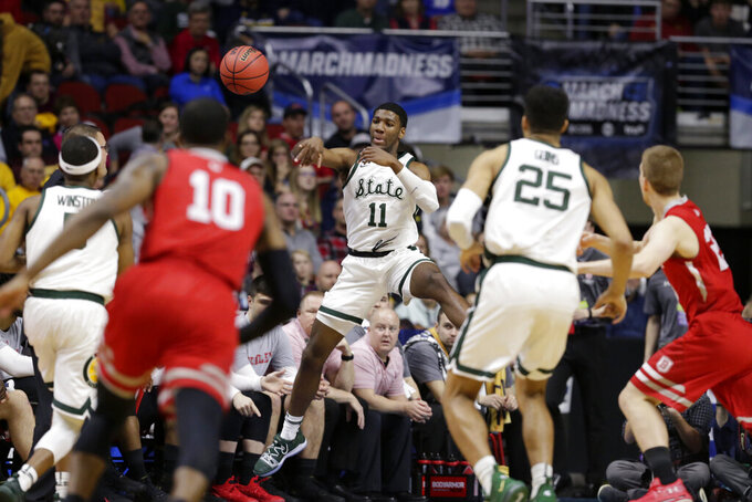 Michigan State's Aaron Henry (11) passes the ball to Cassius Winston (5) during the first half of a first round men's college basketball game against Bradley in the NCAA Tournament in Des Moines, Iowa, Thursday, March 21, 2019. (AP Photo/Nati Harnik)