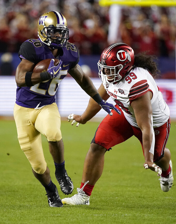 Washington running back Salvon Ahmed (26) runs in front of Utah defensive tackle Leki Fotu (99) during the first half of the Pac-12 Conference championship NCAA college football game in Santa Clara, Calif., Friday, Nov. 30, 2018. (AP Photo/Tony Avelar)
