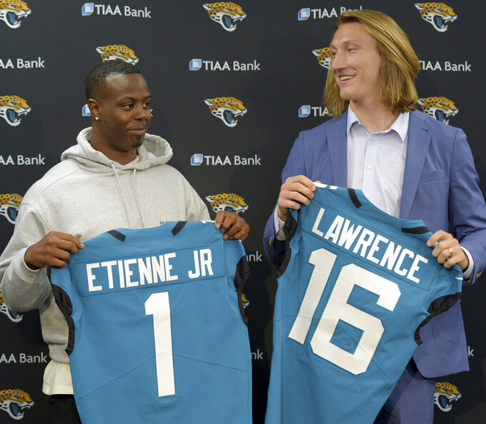 FILE - Former Clemson teammates Travis Etienne and Trevor Lawrence pose with their Jacksonville Jaguars jerseys during an introductory press conference in Jacksonville, Fla., in this Friday, April 30, 2021, file photo.  (Bob Self/The Florida Times-Union via AP, File)