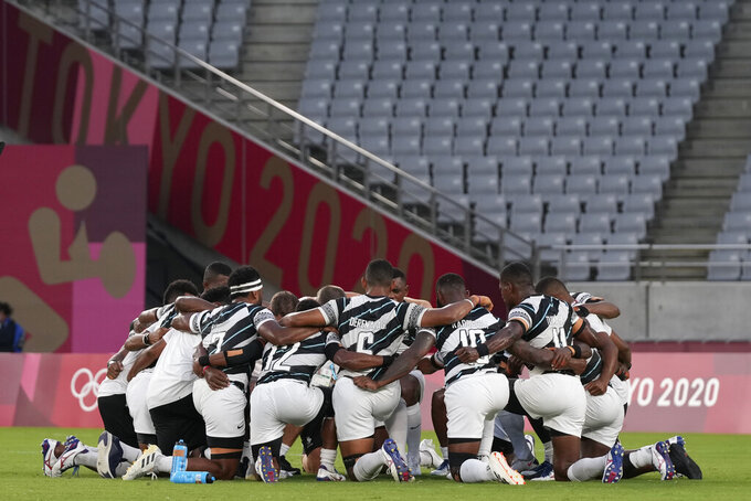 Fiji players huddle up on the pitch after winning their men's rugby sevens gold medal match against New Zealand at the 2020 Summer Olympics, Wednesday, July 28, 2021 in Tokyo, Japan. (AP Photo/Shuji Kajiyama)
