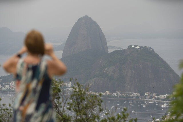 A tourist takes a picture of the Sugar Loaf mountain, in Rio de Janeiro, Brazil, Tuesday, March 17, 2020. The company that administers transport and installations at Rio's Sugarloaf Mountain, another postcard destination that sees 1.5 million visitors annually, said it is closing shop on Tuesday for 15 days as a measure to prevent the spread of the new coronavirus. (AP Photo/Silvia Izquierdo)