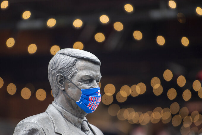 A statue of Harry Kalas wears a face mask during a tour on the COVID-19 protocols and enhanced safety guidelines that fans should be aware of when they return to Philadelphia Phillies baseball games at Citizens Bank Park in Philadelphia, Thursday, March 25, 2021. (Jose F. Moreno/The Philadelphia Inquirer via AP)