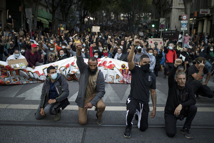 Protesters raise their fists and kneel in front of French riot police during a march against police brutality and racism in Marseille, France, Saturday, June 13, 2020, organized by supporters of Adama Traore, who died in police custody in 2016. Several demonstrations went ahead Saturday inspired by the Black Lives Matter movement in the U.S. (AP Photo/Daniel Cole)