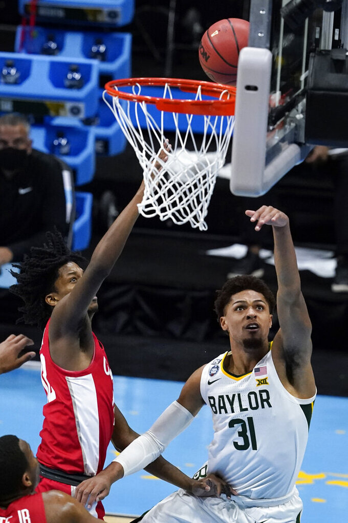 Baylor guard MaCio Teague (31) drives to the basket ahead of Houston guard Tramon Mark, left, during the second half of a men's Final Four NCAA college basketball tournament semifinal game, Saturday, April 3, 2021, at Lucas Oil Stadium in Indianapolis. (AP Photo/Darron Cummings)