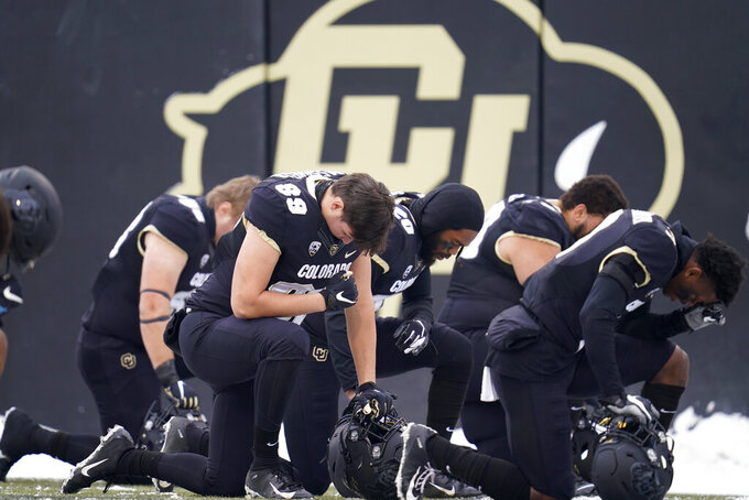 Colorado players share in a moment of silence before hosting Utah in the first half of an NCAA college football game Saturday, Dec. 12, 2020, in Boulder, Colo. (AP Photo/David Zalubowski)