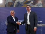 Hungarian Prime Minister Viktor Orban, left, poses with Serbian President Aleksandar Vucic after a press conference in Belgrade, Serbia, Friday, May 15, 2020. Orban is on a one-day official visit to Serbia. (AP Photo/Darko Vojinovic)