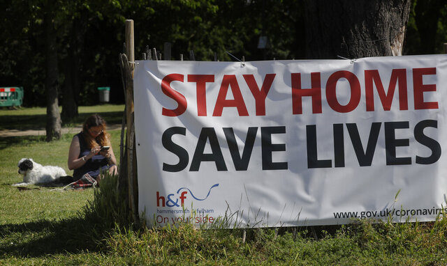 A woman relaxes in a park with her dog near a large sign, in London, Tuesday, May 19, 2020, after the introduction of measures to bring the country out of lockdown amid the coronavirus pandemic. (AP Photo/Kirsty Wigglesworth)