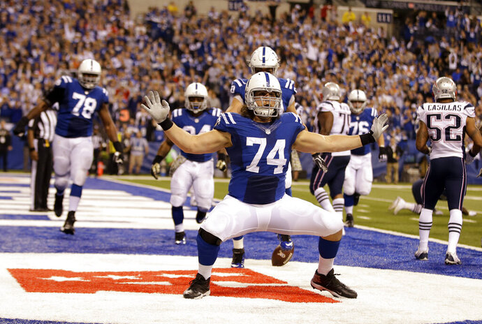 FILE - Indianapolis Colts tackle Anthony Castonzo celebrates after making a catch for a touchdown against the New England Patriots during the second half of an NFL football game in Indianapolis, in this Sunday, Nov. 16, 2014, file photo. Catsonzo, the Colts longtime left tackle, announced his retirement Tuesday, Jan. 12, 2021. The 32-year-old had been an anchor on Indy's offensive line since he was the No. 22 overall draft pick in 2011. (AP Photo/Darron Cummings, File)