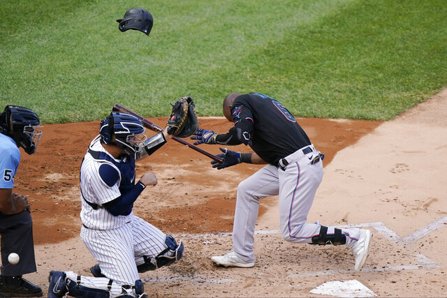 Miami Marlins' Starling Marte (6) ducks after being hit by a pitch that knocked off his helmet as New York Yankees catcher Gary Sanchez, center, and home plate umpire CB Bucknor (54) dodge the ball during a baseball game, Sunday, Sept. 27, 2020, at Yankee Stadium in New York. (AP Photo/Kathy Willens)
