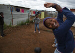 Lilitha Jiphethu, 11, background center, plays with her friends with a ball made from discarded plastic grocery bags, outside her home in Orange Farm, South Africa, on Tuesday, April 28, 2020. Like many children under lockdown, she misses her friends and her teachers, but understands why school is closed and why they are being kept at home. (AP Photo/Denis Farrell)